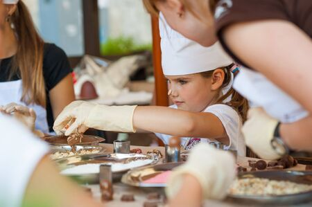 Young girl making chocolate candy photo