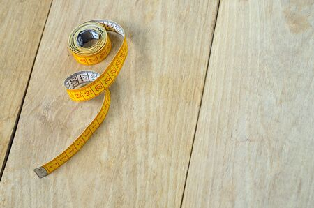 twisted tape measure on wood background photo