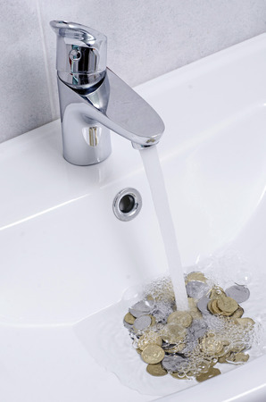 fluent: wash basin and running water from the tap in chrome bathroom, water saving concept Stock Photo