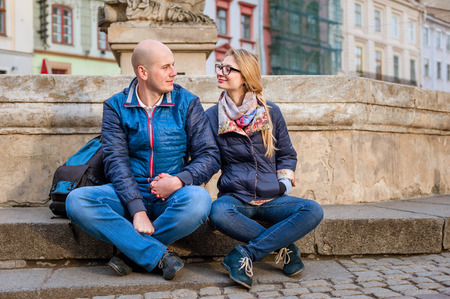 teen legs: Young fashion elegant stylish couple, travel by old European cities, sitting on an old stone, with a backpack, on the square with paving stones