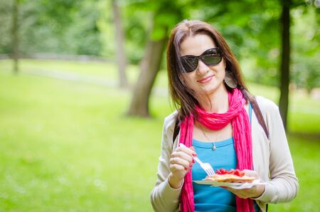 desert: young girl in glasses eats waffles with strawberries, outdoor Foto de archivo