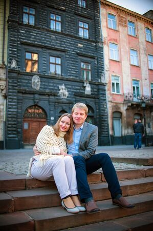 femme romantique: Young fashion elegant stylish couple, travel by old European cities, sitting on an old stone, with a backpack, on the square with paving stones, smiling