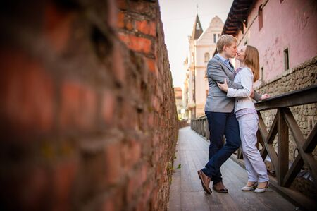street love: Pretty sunny outdoor portrait of young stylish couple while kissing on the street Stock Photo