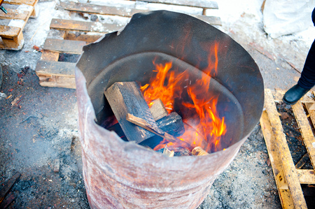 burning firewood in old empty barrel, outdoor Stock Photo