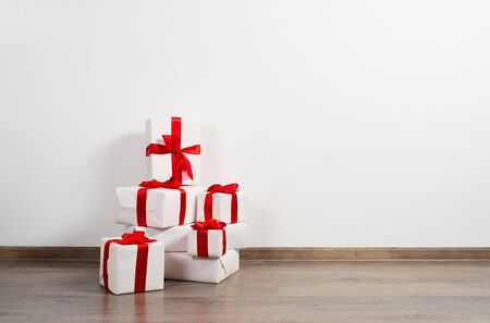surprise party: A pile of Christmas gifts in colorful wrapping with ribbons against the wall on a beautiful hardwood floor with copyspace.