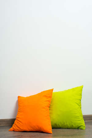 throw cushion: stack of bright pillows on wooden floor