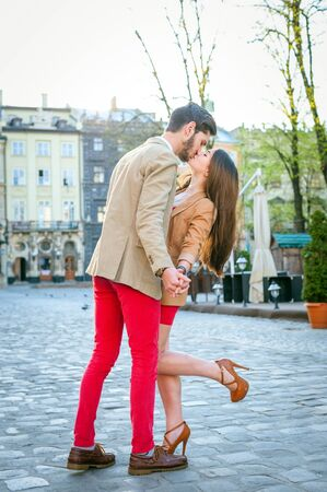 Young fashion elegant stylish sexy couple posing on streets of european city in summer