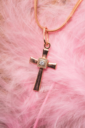 diamond candle: golden cross on a chain on a pink background