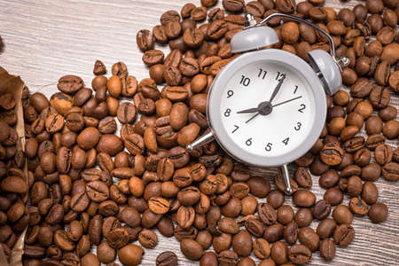 second breakfast: vintage alarm clock and coffee beans on wooden table Stock Photo
