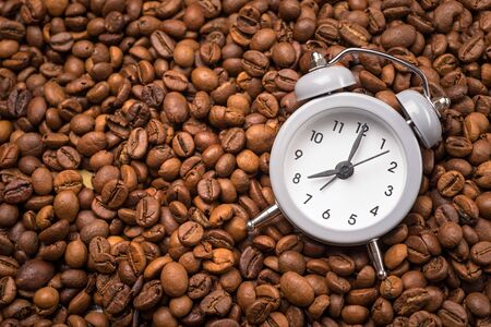 second breakfast: Alarm clock with bells and spilled coffee beans on old wooden table. Focus on dial