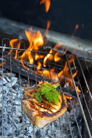 barbequing: beef steak on the grill with flames.