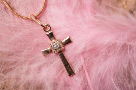 baptize: a smoll golden cross on a chain