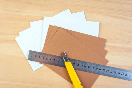 wood cutter: paper cutter and ruler on wood background