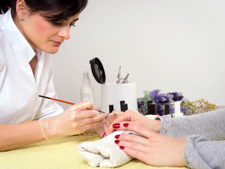 Happy woman getting her nails done at the beauty salon
