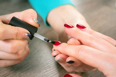 Young beautiful woman in a nail salon receiving a manicure by a professional beautician Stock Photo