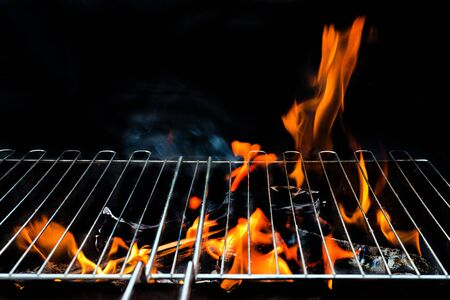 bbq picnic: Hot Empty Charcoal BBQ Grill With Bright Flames On The Black Background. Cookout Concept.