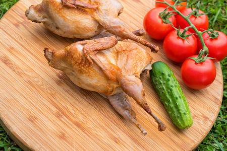 kuropatwa: Delicious fried quail with fresh juicy vegetables on the wooden round board on green grass. Prepared tomato, cucumber, partridge, quail. Roasted Partridge, quail grilling on sunny day. Culinary concept with delicious food. Zdjęcie Seryjne