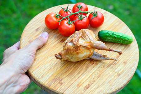 kuropatwa: Delicious fried quail with fresh juicy vegetables on the wooden round board holding in hands. Prepared tomato, cucumber, partridge, quail. Roasted Partridge, quail grilling on sunny day. Picnic on sunny day. Culinary concept.