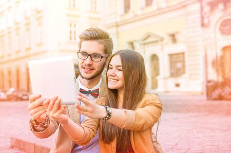 Young smile  couple sitting on stairs in summer , photographs selfie on tablet pc, focus on faces Stock Photo