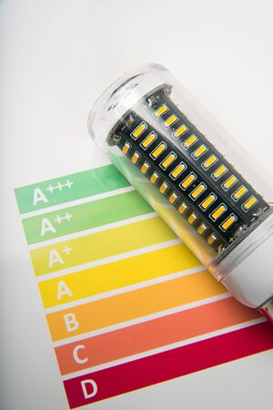 calculating: Energy efficiency concept with energy rating chart and LED lamp on white background Stock Photo
