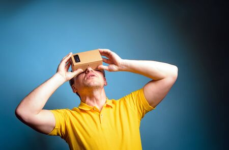 visualizing: Concept of virtual reality carton glasses and interfaces. young man in yellow t-shirt enjoying vr glasses.