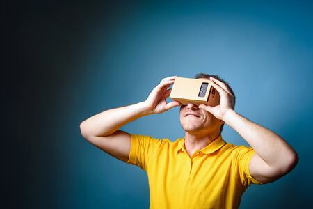 Concept of virtual reality carton glasses and interfaces. young man in yellow t-shirt enjoying vr glasses.