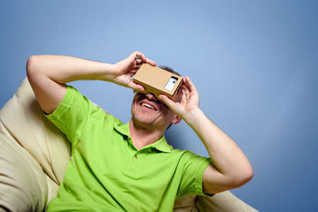 green couch: Concept of virtual reality carton glasses and interfaces. young man in green t-shirt man enjoying vr glasses.