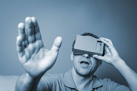 visualizing: Concept of virtual reality carton glasses and interfaces. man enjoying vr glasses.