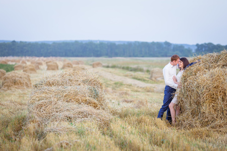 Beautiful young couple is tenderly embracing at rural haystacks summer field background.