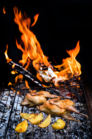 Grilling delicious poultry quails in a restaurant on barbecue. Partridge, quail and potato prepared on the grill on sunny day. Culinary concept with delicious food. Zdjęcie Seryjne