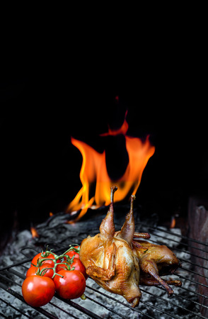 Grilling delicious poultry quails and fresh juicy vegetables in a restaurant on barbecue. Partridge, quail, potato are prepared on the grill on sunny day. Culinary concept with delicious food.
