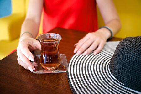 women in red dress with turkish tea on the wooden table