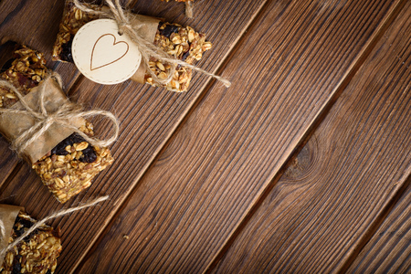 Homemade granola oatmeal energy bars, healthy snack, on wood desk wyth copy space for text