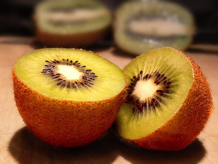 two and a half: Kiwi fruit cut in half with two more halves blurred in the background Stock Photo