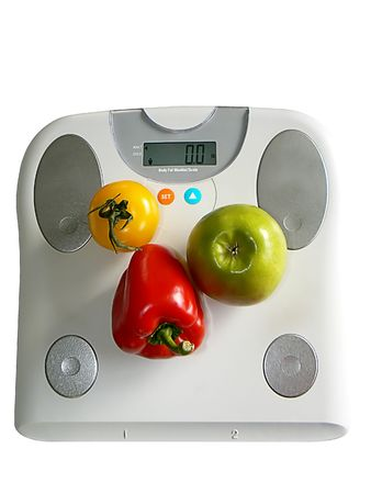 Apple, red pepper and tomato on a fat analyser scale Imagens