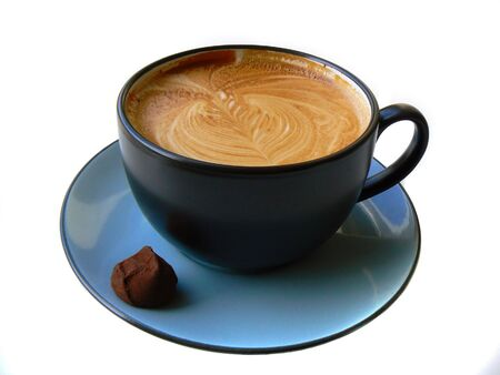 Cup of coffee with artsy image on a surface and chocolate on a plate, over white