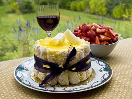Lemon charlotte cake with glass of wine and a bowl of strawberry set on a table overlooking garden