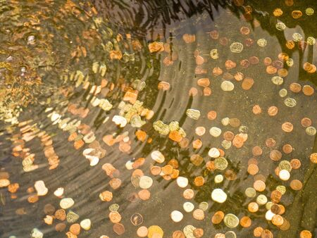 Coins thrown for luck at the bottom of the pool Stock Photo
