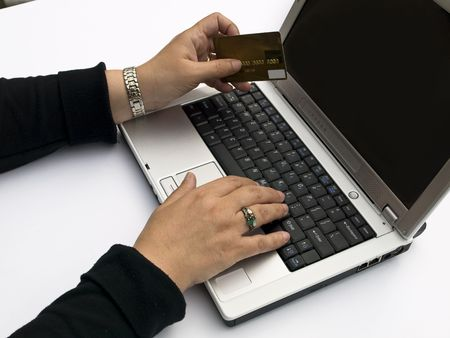 Shopping over the Internet, female hands holding credit card and typing order on a laptop keyboard
