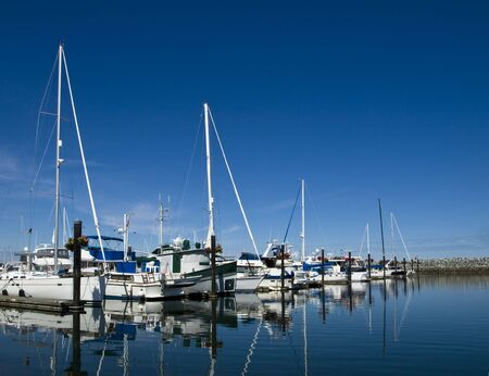 Sailboats in their stalls at marina behind the breakwater