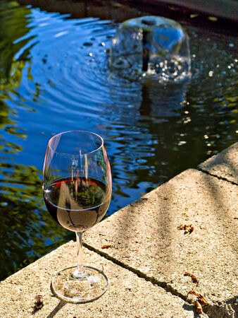 Glass of red wine on the egde of a backyard pond