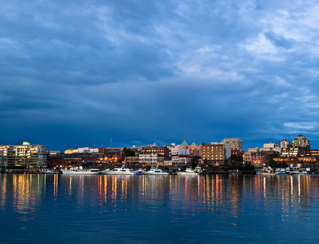 Street lights reflect in water at Inner Harbor, Victoria, BC photo