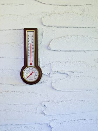 Thermometer on the wall showing comfortable outside temperature and humidity Stock Photo