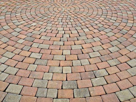 two-colored paving stone creates circular pattern on a plaza