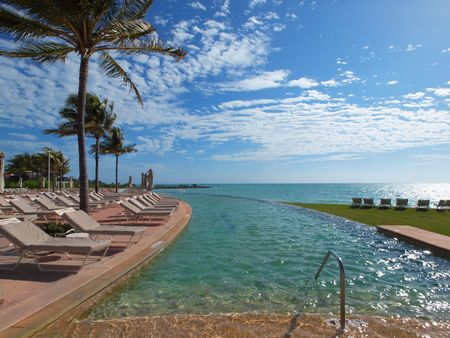 Infinity pool with deck chairs overlooks the ocean in a luxury resort setting Stock Photo - 6297452