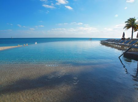 Infinity pool with deck chairs overlooks the ocean in a luurty resort setting