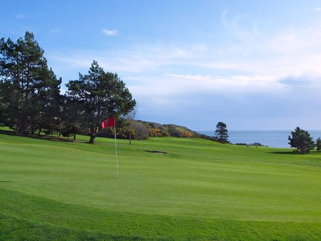 Green grass of golf course located on an ocean shore