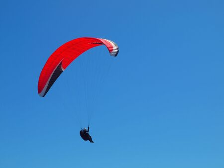paraglider in the sky with red parachute