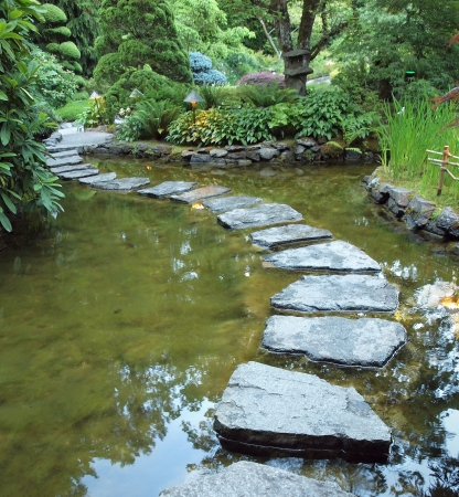 Stepping stones form walking path over the pond at night 写真素材