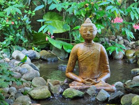 Buddha statue sitting on top of waterfall Stock Photo